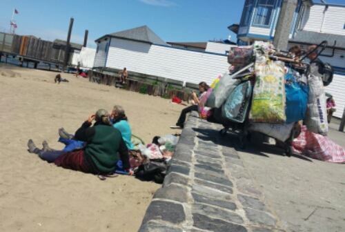 elderly ladies on the beach with shopping carts full of stuff